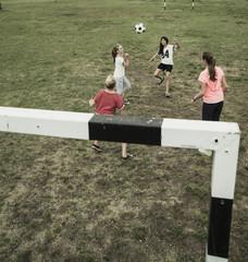 Vier weibliche Teenager-Freunde, die Fußball spielen