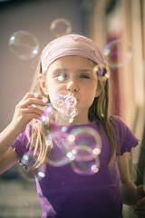 Porträt des kleinen Mädchens, bläst Seifenblasen