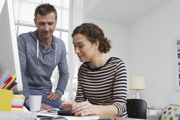 Mann und Frau zu Hause, sitzen am Schreibtisch mit Rechnungen