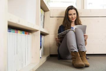 Geschäftsfrau sitzt auf dem Boden mit Magazin