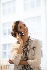 Junge Architektin telefoniert im Büro