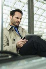 Geschäftsmann am Bahnhof, mit iPad