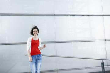 Deutschland, Nordrhein-Westfalen, Köln, Frau steht vor der Fassade im Rheinauhafen