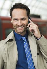 Geschäftsmann am Bahnhof mit Handy