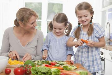 Mutter und Töchter beim Hacken von Gemüse