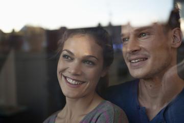 Lächelndes Paar hinter dem Fenster