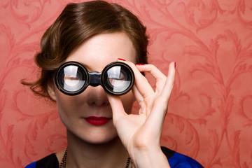 1920's young woman looking through theatre binoculars.