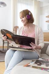 Reife Frau mit Schallplatten und Kopfhörer, Musik hören zu Hause