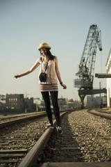 Junge Frau mit alter Kamera balanciert auf Schiene