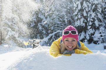 Österreich, Salzburger Land, Altenmarkt-Zauchensee, Lächelnde junge Frau im Schnee liegend