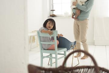 Kleines asiatisches Mädchen sitzt auf einem Stuhl, Mutter und Schwester im Hintergrund