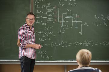 Berufsschüler im Klassenzimmer, Lehrer an der Tafel