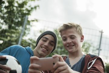 Zwei Freunde mit Fußball, Blick aufs Handy
