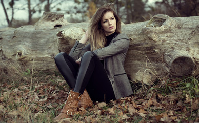 Young girl sitting outdoor in autumn scenery