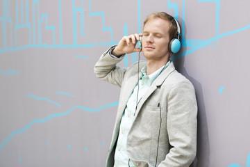 Junger Mann mit Kopfhörern gegen die Wand gelehnt