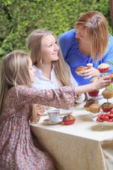 Mutter und ihre beiden Töchter essen Muffins