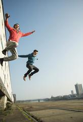 Junger Mann und Teenager springen in die Luft
