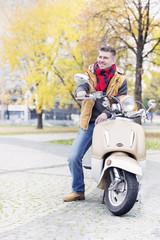 Polen, Warschau, Mann sitzt auf Motorroller