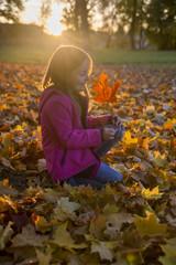 Kleines Mädchen hockend zwischen Herbstlaub im Park