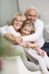 Paar mit Enkelin auf dem Sofa im Wohnzimmer