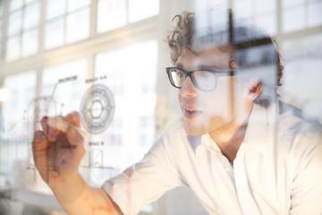 Porträt des jungen Architekten, Kennzeichnung Bauplan im Büro