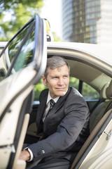 Deutschland, Berlin, Geschäftsmann, der aus dem Taxi aussteigt