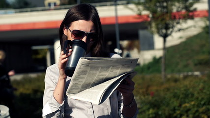 Businesswoman reading newspaper and drinking coffee in the city