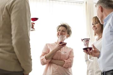Zwei reife Paare trinken Rotwein zu Hause