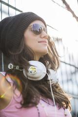 Lächelndes Teenager-Mädchen mit Kopfhörern und Sonnenbrille