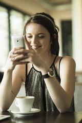 Porträt der jungen Frau mit Smartphone im Café