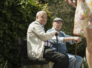 Zwei alte Männer sitzen auf Parkbank, begutachten Beine einer jungen Frau