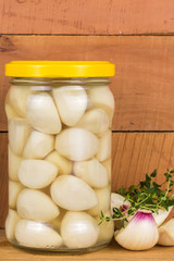 pickled garlic in a jar of green marjoram