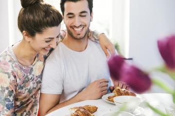Lachendes junges Paar am Frühstückstisch