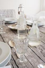 Glas, Wasserflasche und Karaffe auf festlich gedecktem Tisch