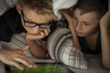 Zwei Jungen liegen auf dem Bett, mit Tablet-PC
