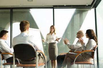 Gruppe von Geschäftsleuten, Hände klatschen für Geschäftsfrau am Flip-Chart