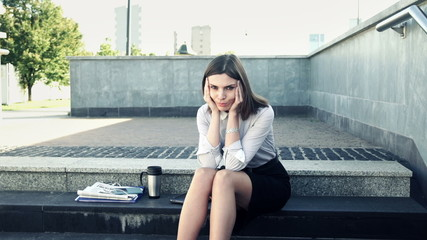 Sad, unhappy businesswoman sitting on stairs in the city
