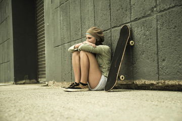 Teenager-Mädchen mit Skateboard an Betonwand