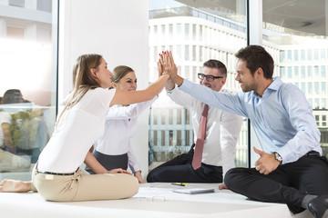 vier erfolgreiche Geschäftsleute am Konferenztisch