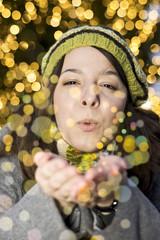 Porträt einer jungen Frau, bläst goldenen Glitter