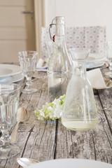 Wasserflasche, Karaffe, Gläser und weißen Blüten auf festlich gedecktem Tisch