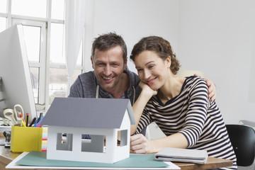 Paar zu Hause mit Hausmodell