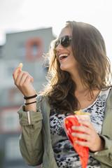 Mädchen mit Sonnenbrille hält Papiertüte mit Pommes