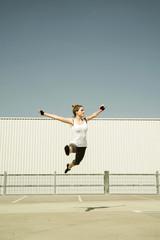Junge Frau springt in die Luft auf Parkebene