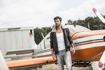 Mann mit Lederjacke steht vor Propellerflugzeug