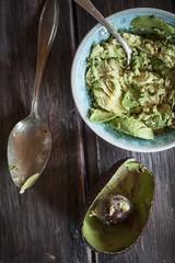 Schüssel zerdrückter Avocado, Löffel und ausgehöhlte Hälfte einer Avocado