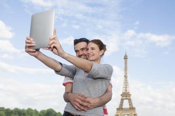 Frankreich, Paris, glückliches Paar fotografiert sich mit Tablet-Computer vor Eiffelturm