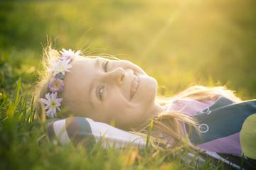 Lächelndes Mädchen auf der Wiese mit Blumen