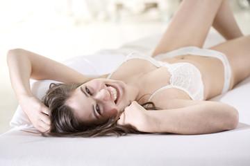 Lächelnde junge Frau in weißem BH und Höschen liegt auf dem Rücken auf dem Bett