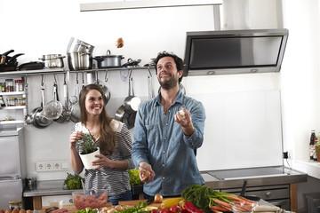 Mann jongliert mit Essen in der Küche